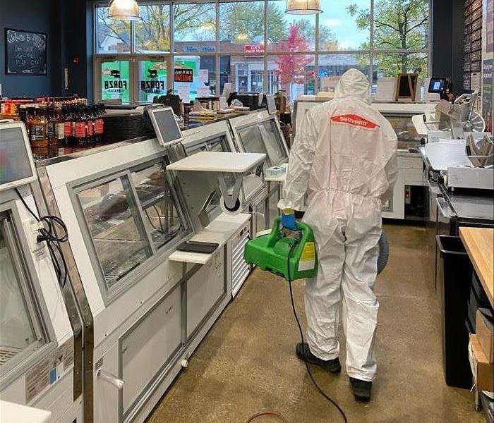 Tech suited up in PPE applies disinfectant inside a butcher shop