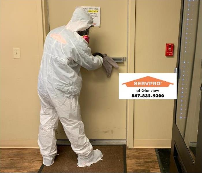 SERVPRO professional wiping down hallway during COVID-19 outbreak