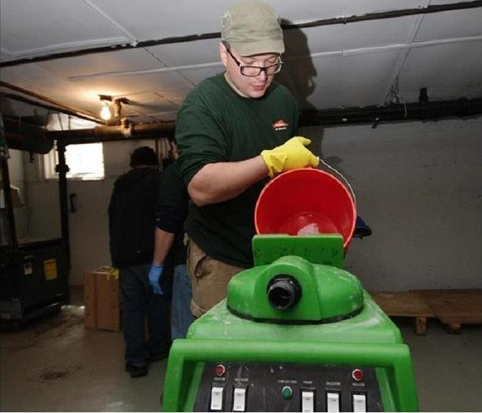Image shows a product technician preparing SERVPRO equipment to clean floors at a customer's home