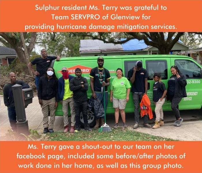 Crew members standing in front of a green SERVPRO van with satisfied customer