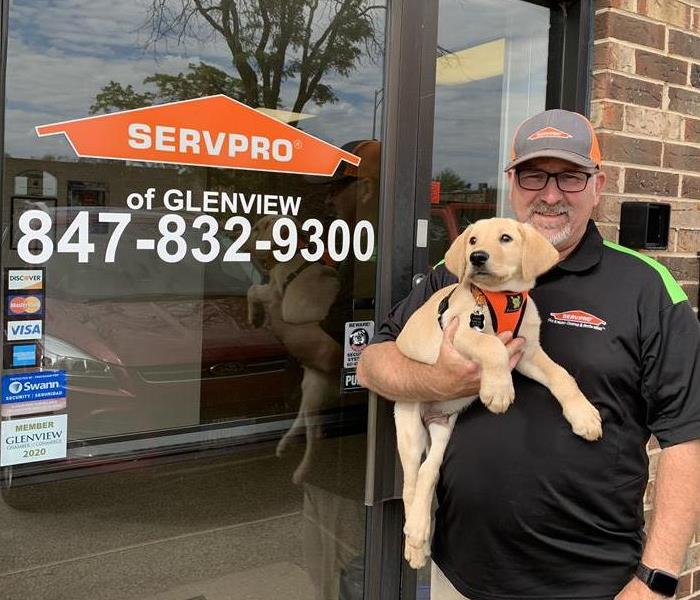 SERVPRO franchise owner standing in front of his office door, holding a 3month old golden lab puppy