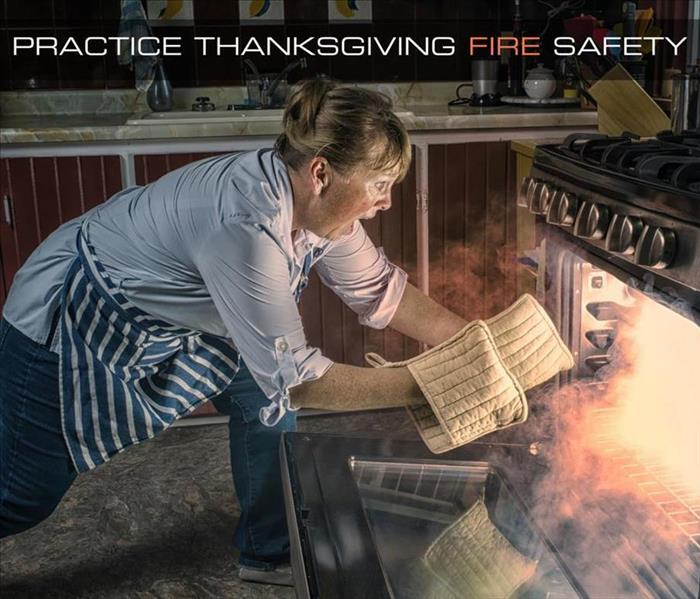 "Panicked woman looking into her open oven at the fire and flames within, with the caption ""Practice Thanksgiving Fire Safety"""